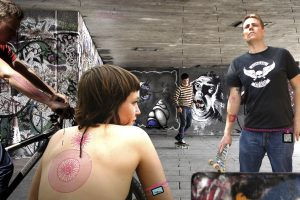 Urban scene with woman with RFID tattoo on back and skateboarder with RFID tattoo on arm.